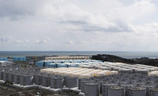 FILE in In this Feb. 27, 2021, file photo, tanks (in gray, beige and blue) store water that was treated but is still radioactive after it was used to cool down spent fuel at the Fukushima Daiichi nuclear power plant in Okuma town, Fukushima prefecture, northeastern Japan. (AP Photo/Hiro Komae, File)