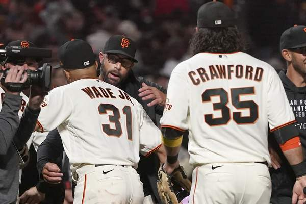 San Francisco Giants manager Gabe Kapler, middle, celebrates with LaMonte Wade Jr. (31) and Brandon Crawford (35) after the Giants defeated the San Diego Padres in a baseball game to clinch a postseason berth in San Francisco, Monday, Sept. 13, 2021. (AP Photo/Jeff Chiu)