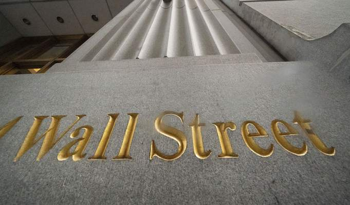 FILE - In this Nov. 5, 2020 file photo, a sign for Wall Street is carved in the side of a building, in New York. (AP Photo/Mark Lennihan, File)