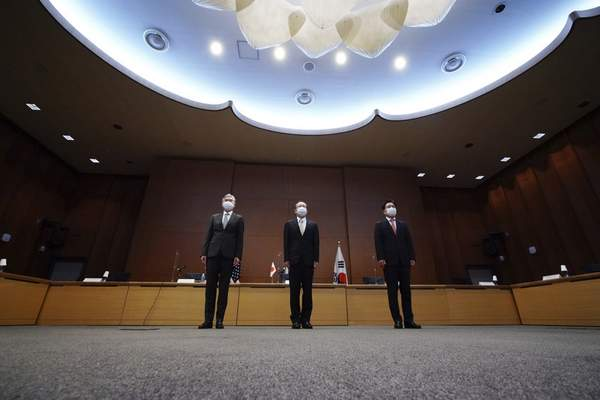 Japanese Foreign Ministry's Director-General of the Asian and Oceanian Affairs Bureau Takehiro Funakoshi, center, U.S. Special Representative for North Korea, Sung Kim, left, and South Korea's Special Representative for Korean Peninsula Peace and Security Affairs Noh Kyu-duk pose for photographers during their trilateral meeting on North Korea at Foreign Ministry Tuesday, Sept. 14, 2021 n Tokyo. (AP Photo/Eugene Hoshiko)