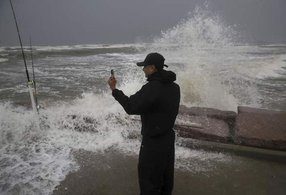 Frank Rivera streams a Facebook live as he fishes with a friend, while Tropical Storm Nicholas heads towards the Texas coast, Monday, Sept. 13, 2021, along the seawall in Galveston, Texas. (Jon Shapley/Houston Chronicle via AP)