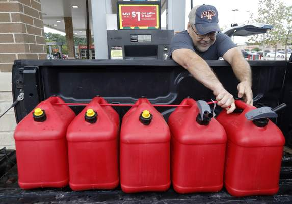 Paul Villagomez secures filled gas containers in his truck as he prepares for Tropical Storm Nicholas, Monday, Sept. 13, 2021, in Kingwood, Texas. I'm just trying to be prepared, Villagomez said. I'm actually surprised there aren't more people filling up. (Jason Fochtman/Houston Chronicle via AP)