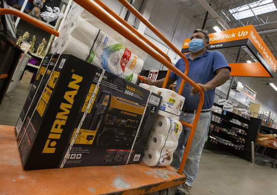 Jose Magia buys a generator for home and work at Home Depot to prepare for Tropical Storm Nicholas, Monday, Sept. 13, 2021, in Houston. (Yi-Chin Lee/Houston Chronicle via AP)