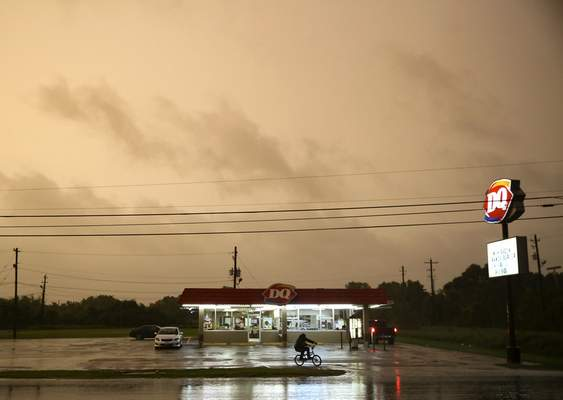 A Dairy Queen in Bay City, Texas, stays open as customers try to get in a meal before it closes as Tropical Storm Nicholas approaches on Monday, Sept. 13, 2021. (Elizabeth Conley/Houston Chronicle via AP)