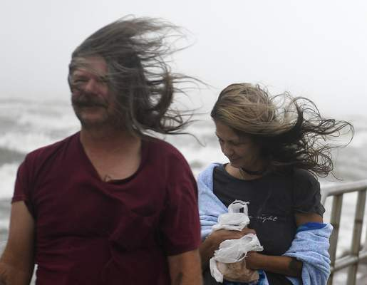 People's hair blows in the wind ahead of Tropical Storm Nicholas, Monday, Sept. 13, 2021, on the North Packery Channel Jetty in Corpus Christi, Texas. (Annie Rice/Corpus Christi Caller-Times via AP)