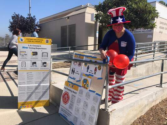 Associated Press Camille Teran-Grange, a polling place volunteer in Los Angeles, adds balloons to voter information placards Tuesday as voters went to the polls to vote on the removal of Gov. Gavin Newsom.