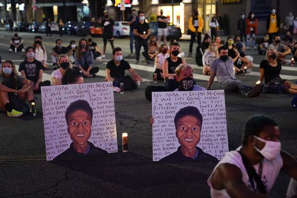 FILE - In this Aug. 24, 2020, file photo, two people hold posters showing images depicting Elijah McClain during a candlelight vigil for McClain outside the Laugh Factory in Los Angeles. (AP Photo/Jae C. Hong, File)