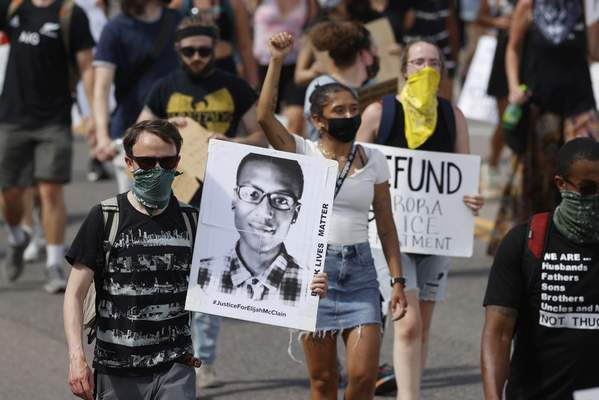 FILE - In this June 27, 2020 file photo, demonstrators carry placards as they walk down Sable Boulevard during a rally and march over the death of Elijah McClain in Aurora, Colo. (AP Photo/David Zalubowski, File)