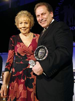 FILE - In this April 8, 2011, file photo, Nan Wooden, left, daughter of former UCLA basketball coach John Wooden, presents Michigan State coach Tom Izzo with the Legends of Coaching Award during the John R. Wooden Award ceremony in Los Angeles. Nan Wooden died Tuesday, Sept. 14, 2021. She was 87. The school said she died of natural causes at a care facility in the San Fernando Valley, according to family members. She had suffered a series of strokes in recent years. (AP Photo/Jason Redmond, File)