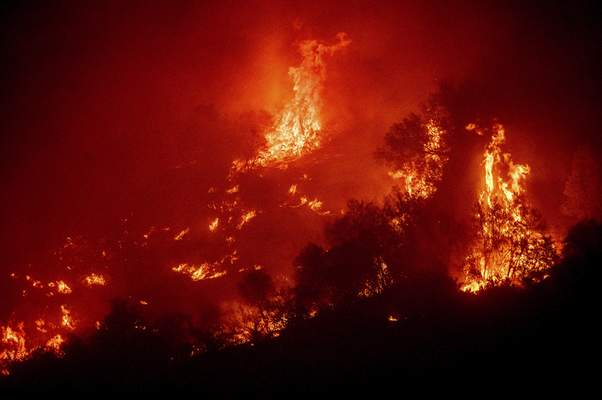 Flames from the KNP Complex Fire burn a hillside above the Kaweah River in Sequoia National Park, Calif., on Tuesday, Sept. 14, 2021. (AP Photo/Noah Berger)