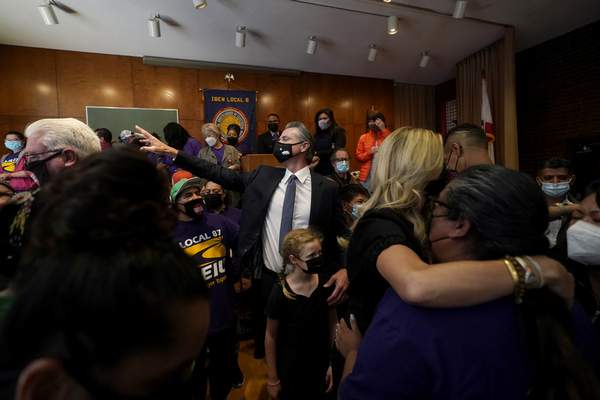Gov. Gavin Newsom, middle, gestures toward supporters with his daughter, Brooklynn, after speaking to volunteers in San Francisco, Tuesday, Sept. 14, 2021. (AP Photo/Jeff Chiu)