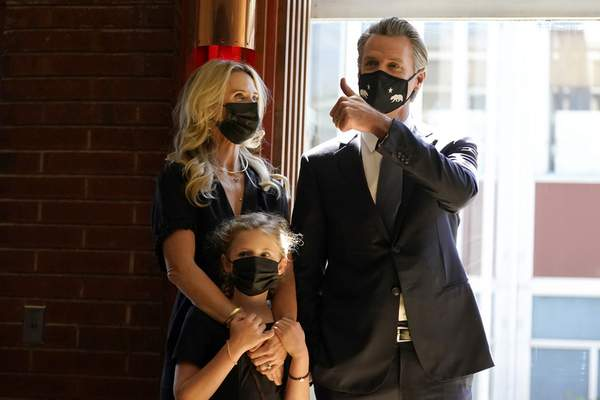 Gov. Gavin Newsom, right, gestures next to his wife, first partner Jennifer Siebel Newsom, and their daughter, Brooklynn, before speaking to volunteers in San Francisco, Tuesday, Sept. 14, 2021. (AP Photo/Jeff Chiu)