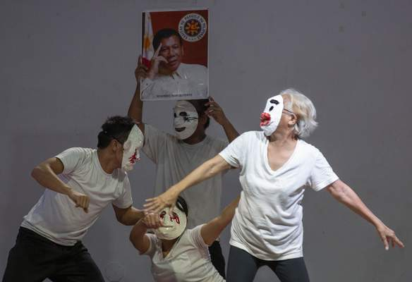 FILE - In this Wednesday, March 4, 2020 file photo, relatives of people killed during the government's war on drugs campaign perform on stage in front of a picture of Philippine President Rodrigo Duterte at a school in metropolitan Manila, Philippines. (AP Photo/Aaron Favila, File)