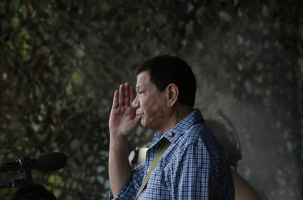 FILE - In this Wednesday Dec. 13, 2018, file photo Philippine President Rodrigo Duterte salutes to soldiers during a ceremony to destroy hundreds of guns and weapons confiscated from pro-Islamic State group siege in Marawi, southern Philippines at the Philippine Army Headquarters in Manila, Philippines. (AP Photo/Aaron Favila)