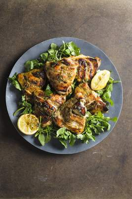 This image released by Milk Street shows a recipe for Chicken Salmoriglio, made with grated lemon zest, garlic, oregano, salt and pepper. (Milk Street via AP)