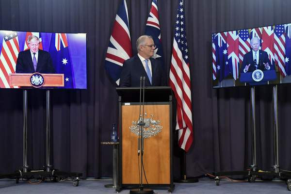 Australia's Prime Minister Scott Morrison, center, appears on stage with video links to Britain's Prime Minister Boris Johnson, left, and U.S. President Joe Biden at a joint press conference at Parliament House in Canberra, Thursday, Sept. 16, 2021. (Mick Tsikas/AAP Image via AP)