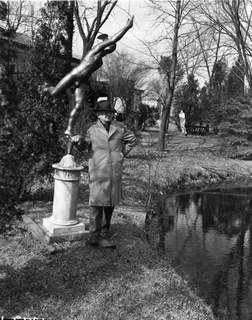 March 26, 1952:Oliver Repp stands with one of his statues next to a pond on his Harlan-area property. (Journal Gazette file photo)