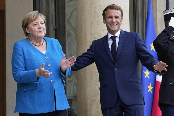 Associated Press French President Emmanuel Macron welcomes German Chancellor Angela Merkel prior to a meeting Thursday at the Elysee Palace in Paris.