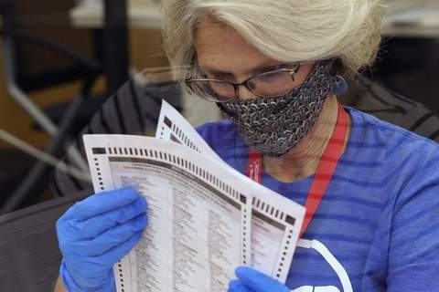 """Not Real News FILE - In this Tuesday, Sept. 14, 2021, file photo, an election worker inspects a ballot for damage before they are sent to be tabulated at the Sacramento County Registrar of Voters Office in Sacramento, Calif. On Friday, Sept. 17, 2021, The Associated Press reported on stories circulating online incorrectly asserting there was fraud in California's recall election because voters were given Sharpie pens or other permanent markers, which the false posts said is illegal and will invalidate ballots. """"Sharpie pens are safe and reliable to use on ballots, and recommended due to their quick-drying ink,"""" reads a Nov. 5 statement from Dominion Voting Systems. """"Regarding potential ink bleed-through, Dominion's systems never allow for the creation of ballots with overlapping vote bubbles between the front and back pages of a ballot."""" (AP Photo/Rich Pedroncelli, File) (Rich Pedroncelli STF)"""