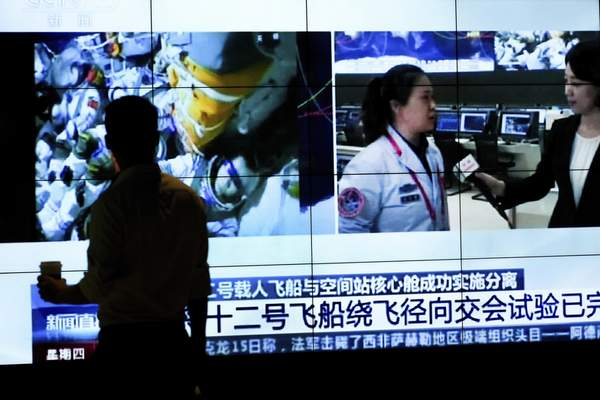 A man is silhouetted as he watches a TV screen showing CCTV broadcasting a news of Chinese astronauts sit inside the Shenzhou-12 manned spacecraft preparing to return to earth, at a shopping mall in Beijing, Thursday, Sept. 16, 2021. (AP Photo/Andy Wong)