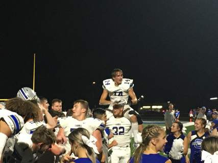 Dylan Sinn | The Journal Gazette Carroll's Aaron Stewart sits on the shoulders of Liam Ottenweller as the team celebrates the Chargers' 42-23 win over Bishop Dwenger at Shields Field on Friday.