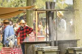 Mike Moore   The Journal Gazette Despite warm temperatures Saturday, members of the Bethany United Methodist Church work around the fire to pop caramel corn during the Johnny Appleseed Festival.