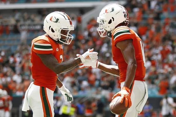 Miami wide receiver Charleston Rambo (11) celebrates with Mike Harley (3) after a touchdown reception during the second quarter of an NCAA college football game against Michigan State, Saturday, Sept. 18, 2021, in Miami Gardens, Fla. (AP Photo/Michael Reaves)