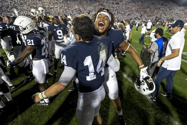Penn State quarterback Sean Clifford (14) and defensive end Davon Townley (18) celebrate the 28-20 victory over Auburn in an NCAA college football game in State College, Pa., on Saturday, Sept. 18, 2021. (AP Photo/Barry Reeger)