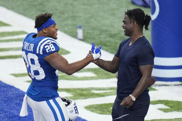 Indianapolis Colts' Jonathan Taylor (28) talks with former Indianapolis Colts running back Edgerrin James before an NFL football game between the Indianapolis Colts and the Los Angeles Rams, Sunday, Sept. 19, 2021, in Indianapolis. (AP Photo/AJ Mast)