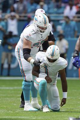 Miami Dolphins quarterback Tua Tagovailoa (1) is assisted by offensive guard Jesse Davis (77), during the first half of an NFL football game against the Buffalo Bills, Sunday, Sept. 19, 2021, in Miami Gardens, Fla. (AP Photo/Hans Deryk)