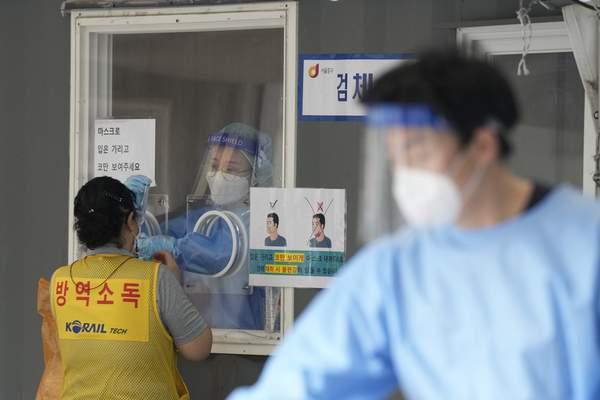 A medical worker in a booth takes a nasal sample from a disinfection worker during coronavirus testing at a makeshift testing site in Seoul, South Korea, Sunday, Sept. 19, 2021. The letters on a jacket read, Disinfection. (AP Photo/Ahn Young-joon)