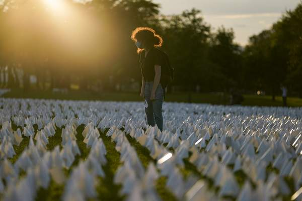 Zoe Nassimoff, of Argentina, looks at white flags that are part of artist Suzanne Brennan Firstenberg's temporary art installation, In America: Remember, in remembrance of Americans who have died of COVID-19, on the National Mall in Washington, Friday, Sept. 17, 2021. Nassimoff's grandparent who lived in Florida died from COVID-19. (AP Photo/Brynn Anderson)