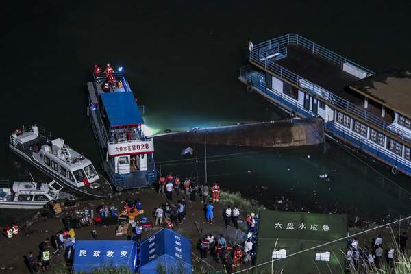 In this photo released by Xinhua News Agency, rescuers conduct search and rescue at the site of an overturned passenger ship in Liupanshui in southwest China's Guizhou province, Sunday, Sept. 19, 2021. (Ou Dongqu/Xinhua via AP)