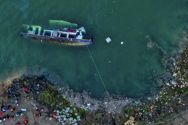 In this photo released by Xinhua News Agency, rescuers work at the site of an overturned passenger ship in Liupanshui in southwest China's Guizhou province, Sunday, Sept. 19, 2021. (Ou Dongqu/Xinhua via AP)