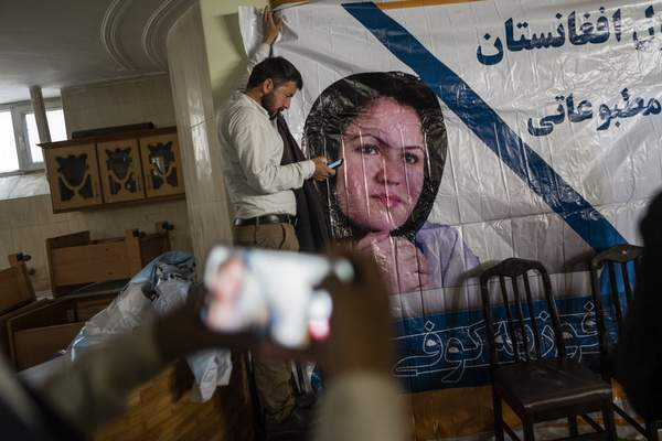 A man holds a poster of Afghan politician Fawzia Koofi prior to a press conference organized by the movement of change for Afghanistan Party in Kabul, Afghanistan, Sunday, Sept. 19, 2021. (AP Photo/Bernat Armangue)