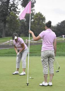 Michelle Davies | The Journal Gazette Marta Zoller, of Fort Wayne, holds the flag as Tara Armstrong putts on the 2nd hole at the Fort Wayne Country Club for Monday's Vera Bradley Foundation for Breast Cancer Classic.