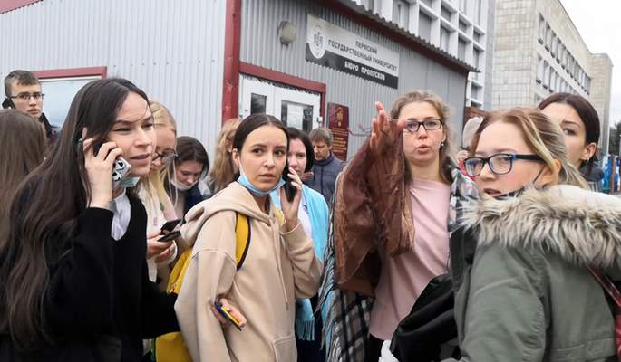 In this grab taken from video, a group of students react and speak on their phones near the Perm State University in Perm, about 1,100 kilometers (700 miles) east of Moscow, Russia, Monday, Sept. 20, 2021. A gunman opened fire in a university in the Russian city of Perm on Monday morning, leaving at least eight people dead and others wounded, according to Russia's Investigative Committee. (AP Photo)