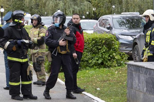 An armed police officer, center, and firefighters gather at the Perm State University in Perm, about 1,100 kilometers (700 miles) east of Moscow, Russia, Monday, Sept. 20, 2021. A gunman opened fire in a university in the Russian city of Perm on Monday morning, leaving at least eight people dead and others wounded, according to Russia's Investigative Committee. (AP Photo/Anastasia Yakovleva)