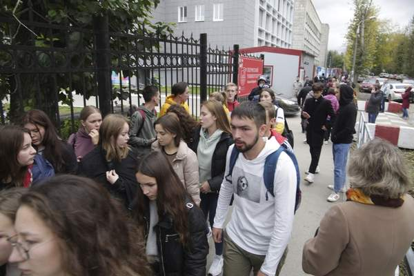 A group of students gather near the Perm State University in Perm, about 1,100 kilometers (700 miles) east of Moscow, Russia, Monday, Sept. 20, 2021. A gunman opened fire in a university in the Russian city of Perm on Monday morning, leaving at least eight people dead and others wounded, according to Russia's Investigative Committee. (AP Photo/Anastasia Yakovleva)