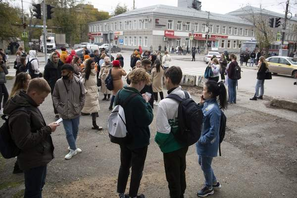 A group of students gather at the Perm State University in Perm, about 1,100 kilometers (700 miles) east of Moscow, Russia, Monday, Sept. 20, 2021. A gunman opened fire in a university in the Russian city of Perm on Monday morning, leaving at least eight people dead and others wounded, according to Russia's Investigative Committee. (AP Photo/Anastasia Yakovleva)