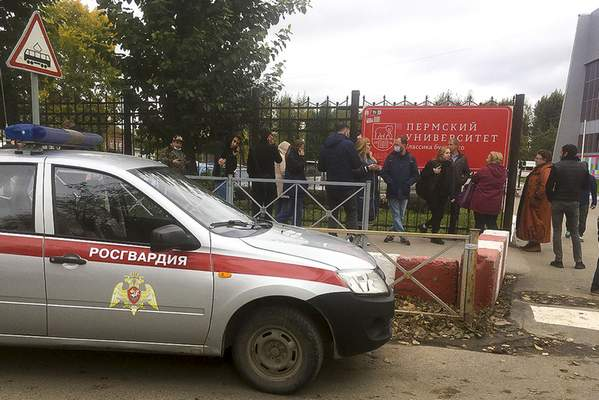 People stand behind the fence near the Perm State University, in Perm, Russia, Monday, Sept. 20, 2021. A gunman opened fire in a university in the Russian city of Perm on Monday morning, leaving at least five people dead and others wounded, according to Russia's Investigative Committee. (AP Photo/Anastasia Yakovleva)