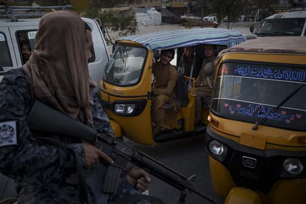 Associated Press Drivers and passengers stuck in a traffic jam watch Taliban fighters riding in the back of a pickup Monday in Kabul, Afghanistan.