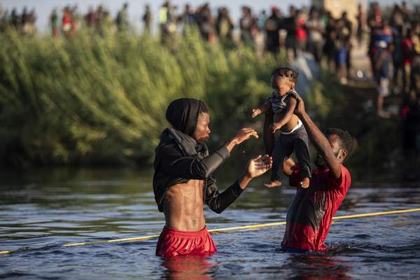 Associated Press Men lift a baby over the waters of the Rio Grande on Monday as migrants, many from Haiti, wade from Del Rio, Texas,back to Ciudad Acuña, Mexico, to avoid deportation from the U.S.