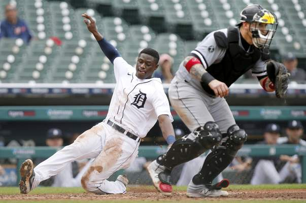 Detroit Tigers' Daz Cameron scores behind Chicago White Sox catcher Yasmani Grandal during the fourth inning of a baseball game Tuesday, Sept. 21, 2021, in Detroit. (AP Photo/Duane Burleson)