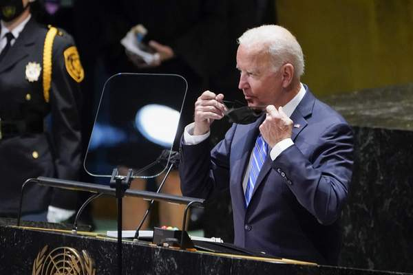 President Joe Biden takes off his face mask before addressing the 76th Session of the United Nations General Assembly, Tuesday, Sept. 21, 2021, in New York. (AP Photo/Evan Vucci)