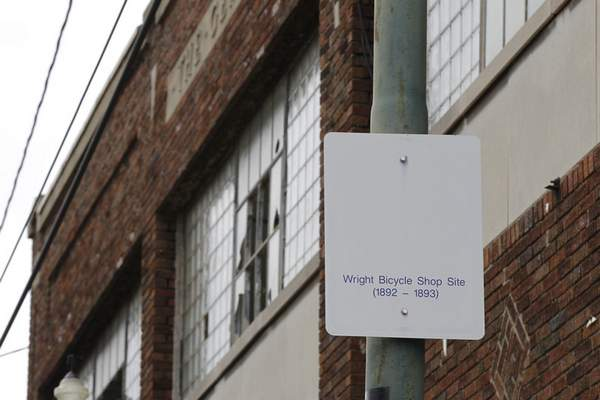 In this undated photo, a sign notes the site of the Wright brothers' bike shop outside the former Gem City Ice Cream building in Dayton, Ohio. (Ty Greenlees/Dayton Daily News via AP, File)