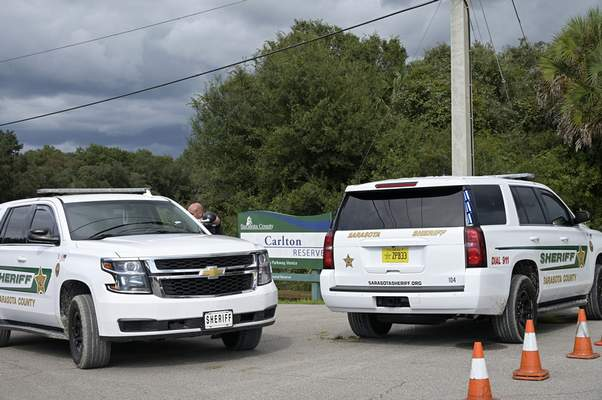 Sarasota County Sheriff's Office vehicles sit at the the entrance of the Carlton Reserve during a search for Brian Laundrie, Tuesday, Sept. 21, 2021, in Venice, Fla. (AP Photo/Phelan M. Ebenhack)