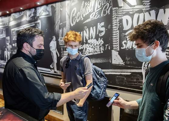 Jimmy Staveris, left, manager of Dunn's Famous restaurant scans the COVID-19 QR code of a client in Montreal on Sept. 1, 2021, as the Quebec government's COVID-19 vaccine passport comes into effect. (Graham Hughes/The Canadian Press via AP)