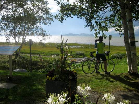 FILE - A cyclist takes in the St. Lawrence vista at Notre-Dame-du-Portage, Quebec, on Aug. 12, 2015. (AP Photo/Cal Woodward, File)
