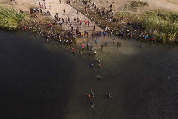 Migrants, many from Haiti, are seen wading between the U.S. and Mexico on the Rio Grande, Tuesday, Sept. 21, 2021, in Del Rio, Texas. (AP Photo/Julio Cortez)